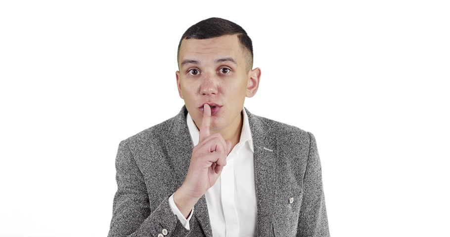 Handsome young man doing Hush sign with finger on lips, looking at camera. Gesture of Silence on a white background.