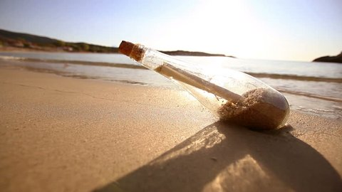 Message in a bottle on sand beach at sunset. Help and communication