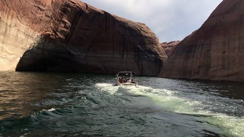 Boat drives across lake surrounded by cliff walls. Beautiful Lake Powell boasts amazing scenery with its vast landscape and red rock cliffs.