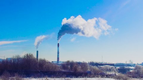 smoke from a chimney factory frosty in the winter against a background of blue sky ecology mud greenhouse effect
