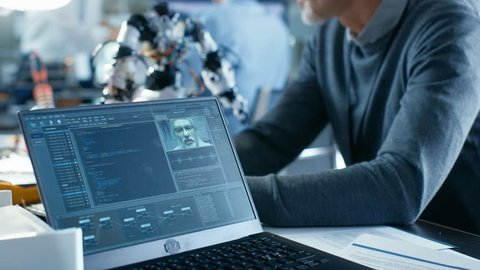 Senior Robotics Engineer Manipulates Voice Controlled Robot, Laptop Screen Shows Software Using Machine Learning Technique. In the Background Robotics Research Center Laboratory.