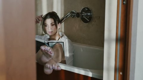 Girl reading a book in the bathroom