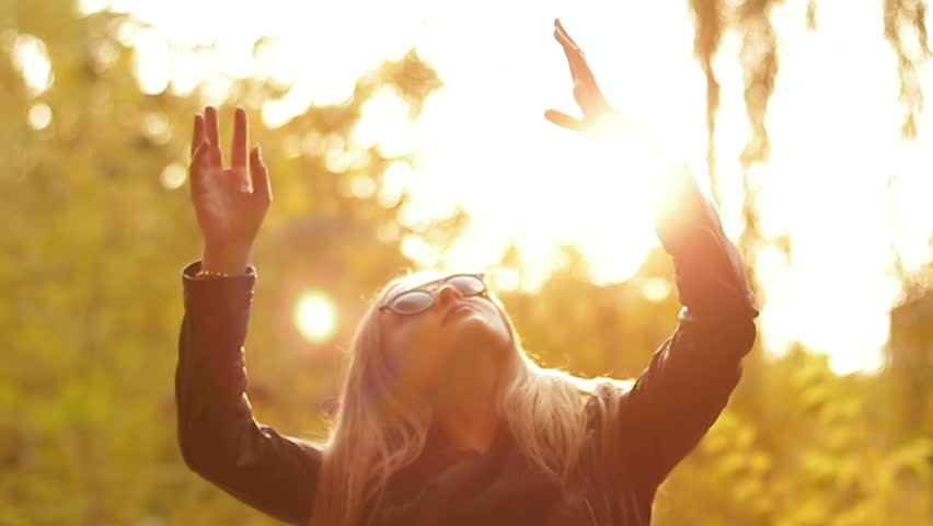 Silhouette of a girl in sunglasses at sunset. She lifting her hands up to the sun and enjoying the warmth. Young woman playing with sunlight at sunset #1007896408