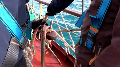 Crew making knots and hitches on tall ship