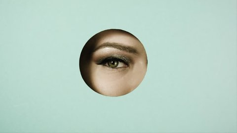 Girl's eye with beautiful make-up,with sparkles,with shadows, peeps through circular crevice of colored paper. Girl's eye is in the round. Closes and opens palm her eyes. Concept advertising.