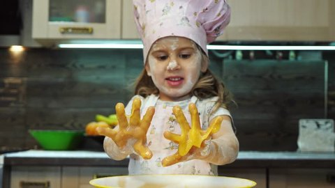 Pretty kid having fun in the kitchen and mixing pastry batter with hands.