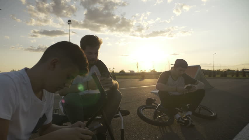Bikers boys resting after cycling race checking smartphones watching social media network news