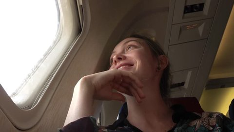 Girl at the porthole in the plane. Young woman on passenger seat near window in airplane