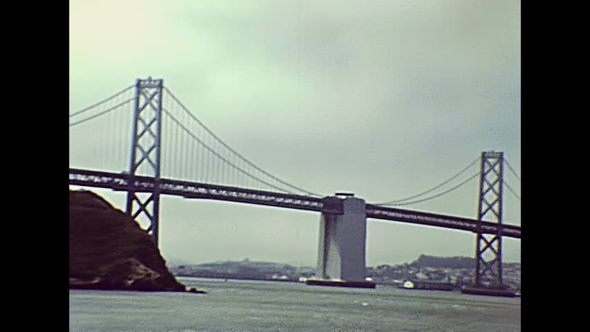 Oakland Bay Bridge seen from Treasure Island with San Francisco skyline with Transamerica building and Coit tower of an archival footage in 1980s. San Francisco, California, United States in 1980.