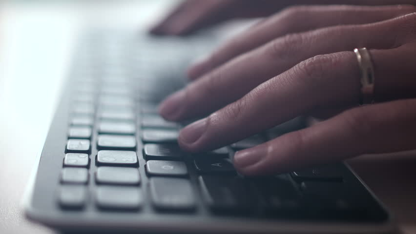 Computer keyboard. Person is writing on the keyboard. The camera is in motion - on dolly. Close-up, counter-light, low depth - film depth of field. Filmed using film lenses.