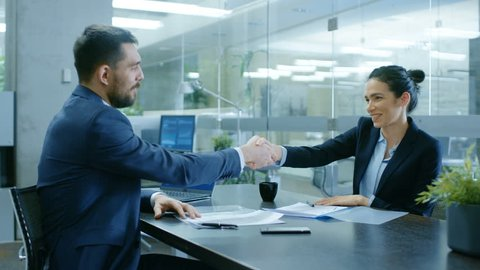 Businesswoman and Businessman Have Conversation. Draw up a Contract, Sign Documents, Seal the Deal, Finish Transaction, Come to an Agreement. They're in Modern Conference Room. Shot on RED EPIC-W 8K.
