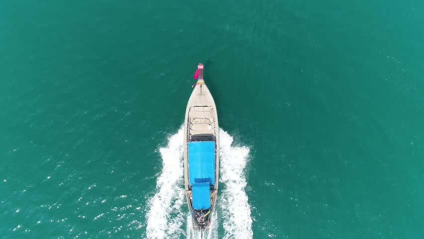 Sun rays in the water. Bird Eye View Aerial Drone Asian Tradition Boat Floating on Clear Blue Ocean