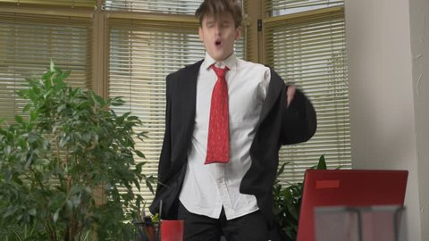 Young man in a suit dances in the office, makes funny faces, fools around, rejoices. Work in the office concept 60 fps