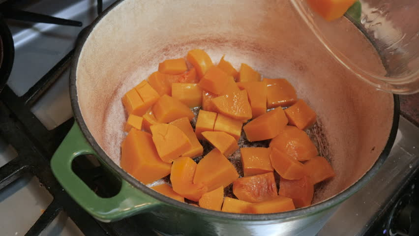 Sautéing butternut squash cubes in a dutch oven 4k. The chunks of the bright orange gourd cook in butter in the heavy saucepan. The recipe video shows step by step of making an autumn vegetable soup