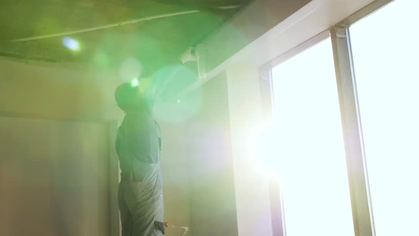 Painter working with paint roller to paint the wall of a room. Do it yourself concept. Man paints the wall with a roller at the window