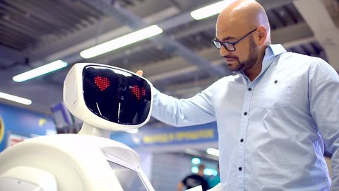 Visitors man talking with humanoid robot. slow-motion. A robot with a display shows emotions, talking, confesses in love. Robot fell in love, the emotions. artificial intelligence, virtual love, vr
