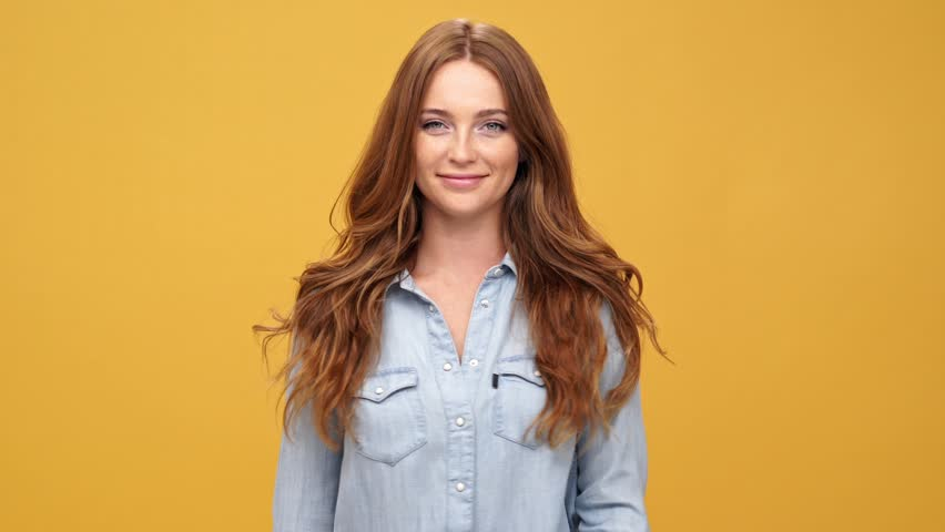 Happy ginger woman in denim shirt waving and showing peace gesture at camera over yellow background