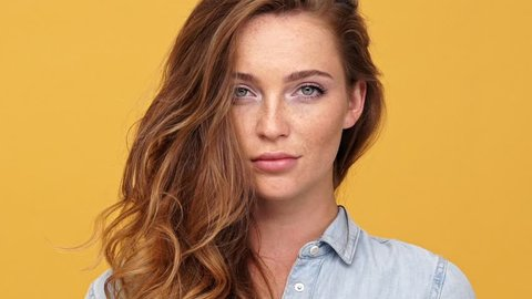 Close up of Mystery ginger woman in denim shirt posing and looking at the camera over yellow background