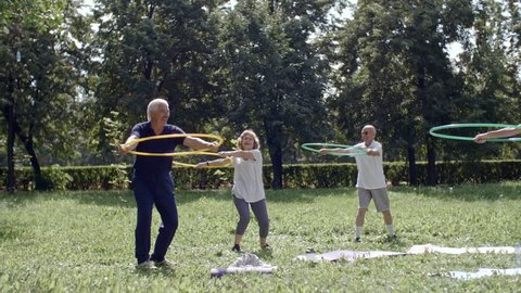 Group of senior people holding hula hoops in front of themselves and performing torso rotation exercises with their trainer
