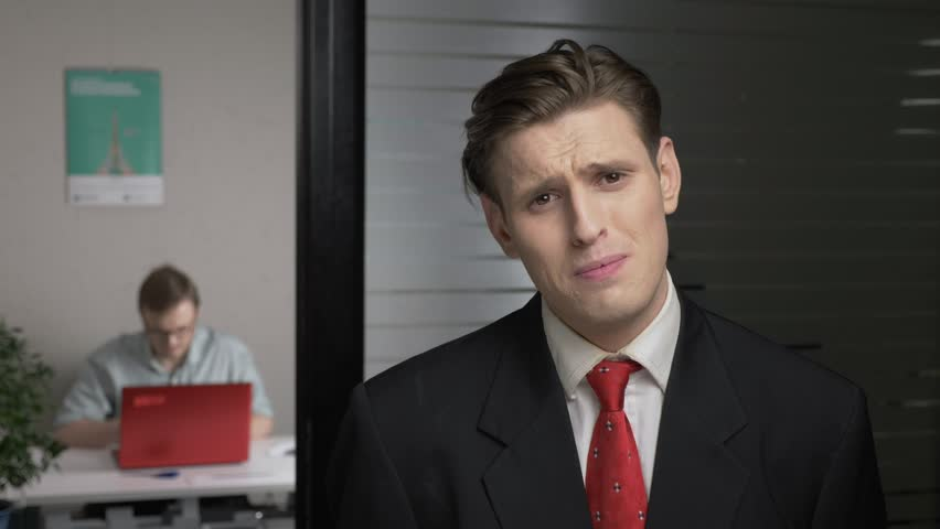 Young successful man in a suit shows no by shaking head, upset, crying. Man works on a computer in the background. 60 fps