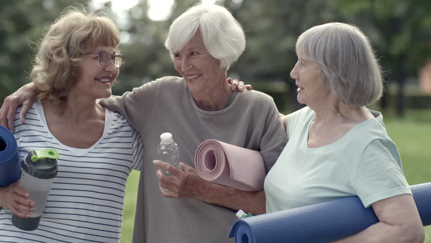 Tracking shot of three senior ladies holding yoga mats and water bottles, hugging and talking to each other in park
