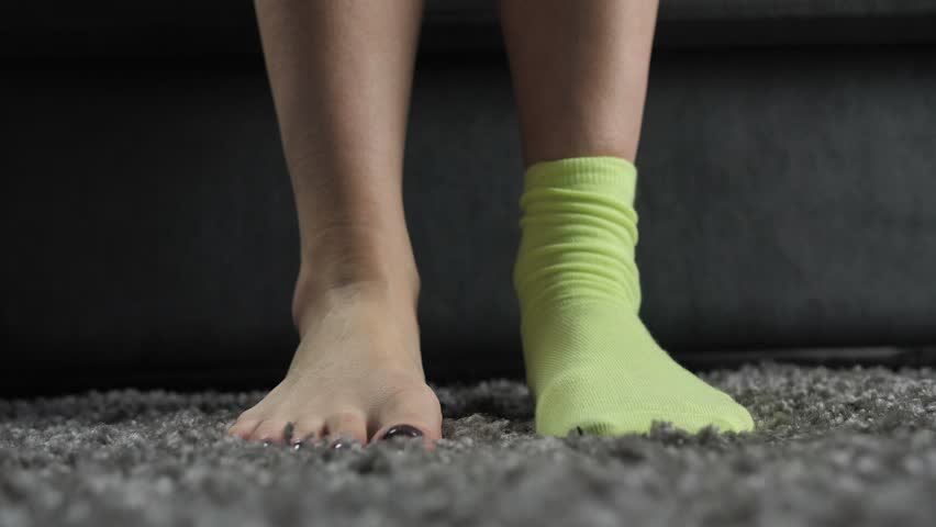 Close-up of woman's hands putting on mismatched socks of different color on her feet. Woman wearing different colored socks on the carpet. Uniqueness, difference and independance concept. Front view