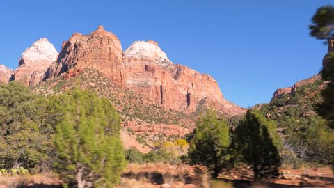 In movement, view from the car. Moving near high mountain offering amazing nature views of the red rocks of the canyon . At Zion National Park, Utah, USA. Slow motion, 3840x2160, 4K.