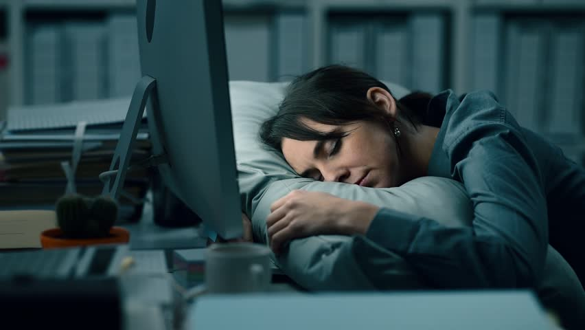 Tired exhausted office worker sleeping on the desk at work: she is waking up, yawning and checking the computer | Shutterstock HD Video #1008065368