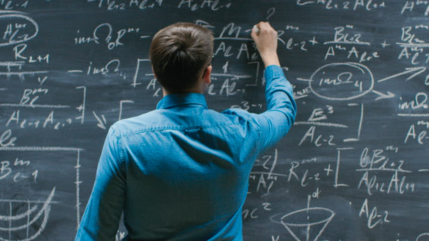 Brilliant Young Mathematician Approaches Big Blackboard and Finishes writing Formula, Turns Around and Smiles on Camera. Shot on RED EPIC-W 8K Helium Cinema Camera.