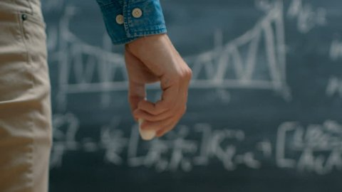 Brilliant Young Academic Finishes Writing Complex Mathematical Formula/ Equation on the Blackboard. Shot on RED EPIC-W 8K Helium Cinema Camera. Shot on RED EPIC-W 8K Helium Cinema Camera.