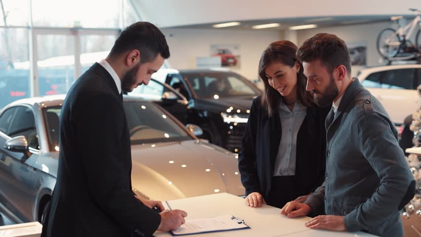 Happy young couple buying new car. Seller of machines and buyer shaking hands, putting in turn signatures in contract. Seller of machines making successful deal.