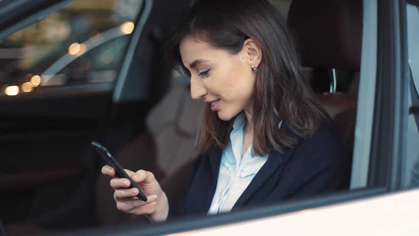 Beautiful young woman with dark short hair sitting in car salon. Girl looking at screen of smartphone, reading message from boyfriend. Smiling. Chatting. | Shutterstock HD Video #1008068068