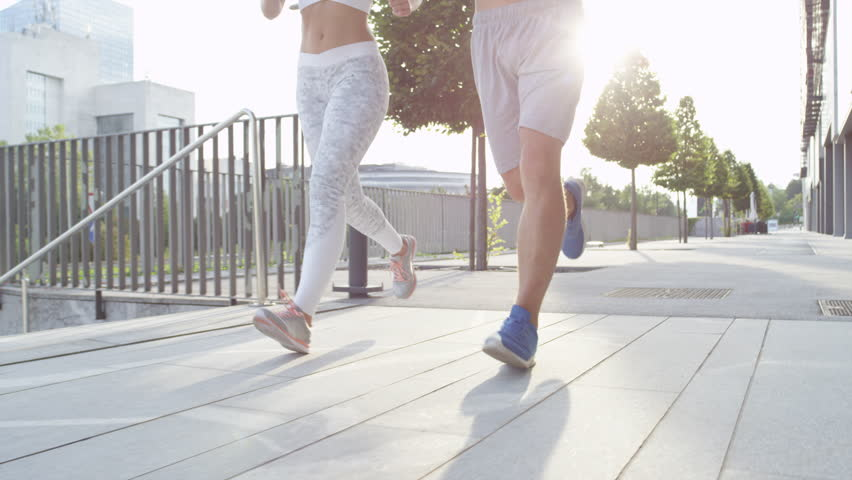 SLOW MOTION CLOSE UP LENSE FLARE: Unrecognizable fitness couple running together on sunny city streets after long day at office. Athletic newlyweds exercising together. Young guy and girl working out. | Shutterstock HD Video #1008074848