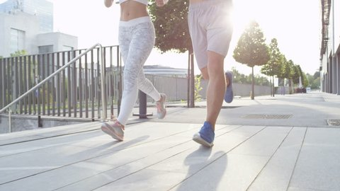 SLOW MOTION CLOSE UP LENSE FLARE: Unrecognizable fitness couple running together on sunny city streets after long day at office. Athletic newlyweds exercising together. Young guy and girl working out.