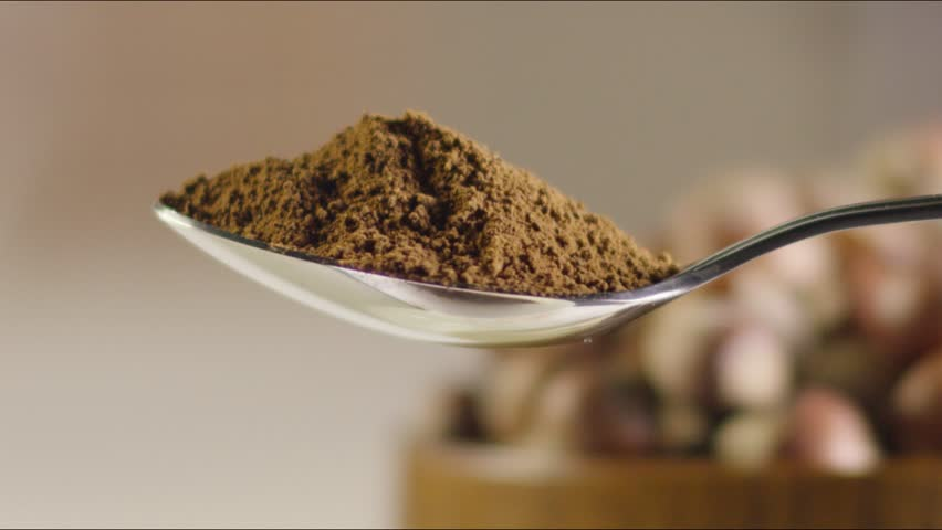 a full spoon of coffee. against the background of hazelnuts. slow