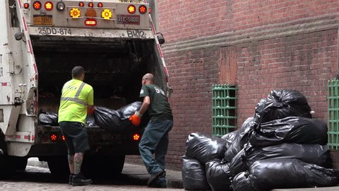 NEW YORK CITY, NY - JUNE 6: Loading garbage truck with black trash bags in downtown New York City, New York June 6, 2016 taken in 4k/UHD resolution.