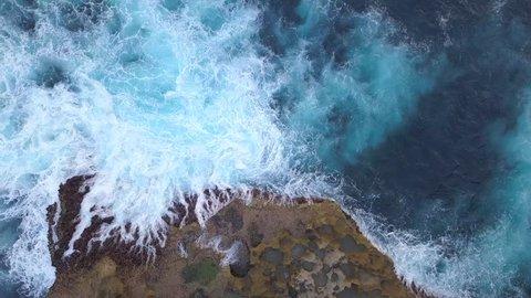 Aerial: Angels Billabong Natural Pool. Big Blue Sea Waves Crashing on Rock Cliff at Tropical Island. 4K Travel Footage. Nusa Penida, Bali, Indonesia.