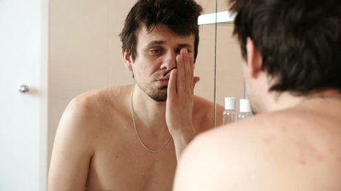 Sleepy man looking at the mirror. Tired man who has just woken up gets ready for his morning shower