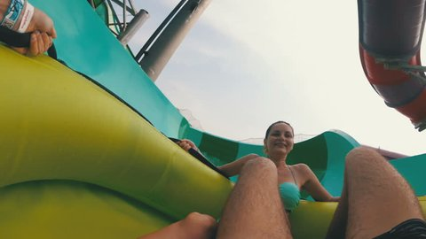 Water slides pov. The guy with the girl on the inflatable circle descends from the water slides.