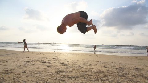 Young man doing parkour tricks on sea beach at sunset. Freerunner guy showing various jumps while running on ocean shore at sundown. Acrobatic stunts and somersaulting on sunny summer day. Slow motion