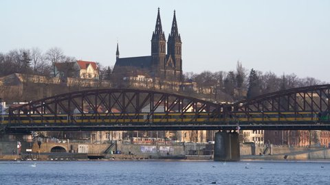 A view of Prague's castle Visehrad and the Vltava river on a winter day. Train pass over a bridge