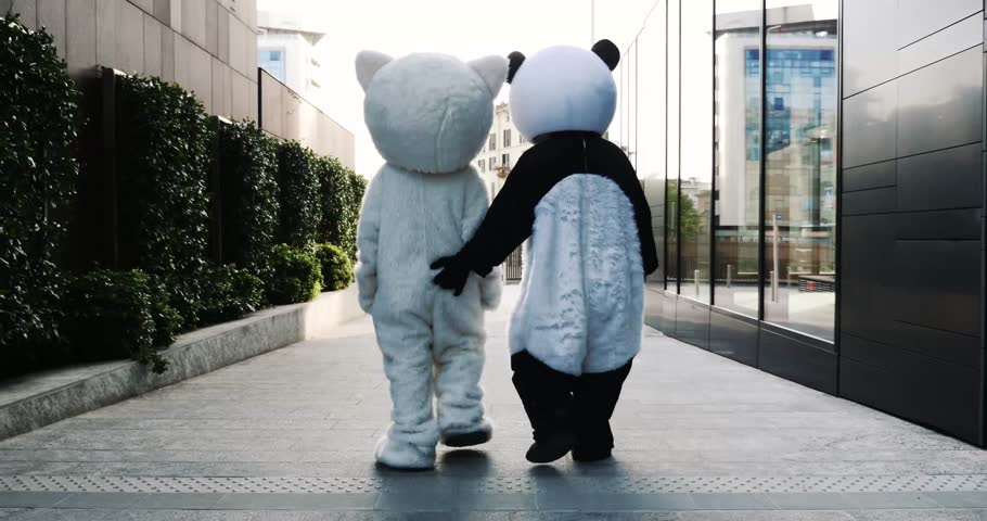 Two friends wearing animal costumes walking and having fun in the city