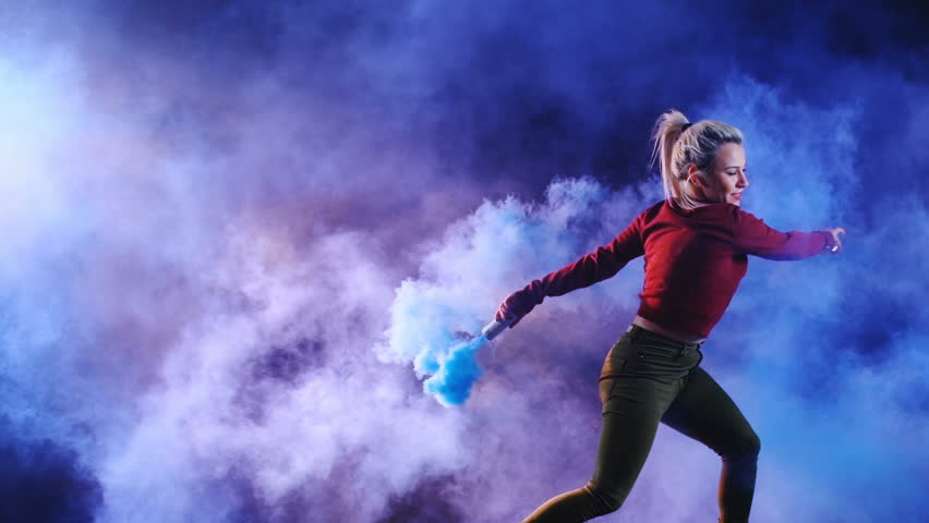 4K girl holding a color smoke grenade. backstage shooted moment for happy comedy and parody projects. Slow motion 150fps.