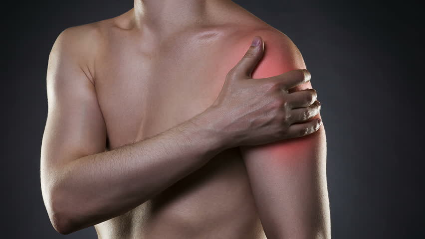 Man with pain in shoulder on black background, studio shot with red dot