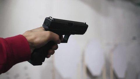 Gun is shot close-up. Pistol in hand close-up. Pistol being shot 1 times. Man shoots a black gun