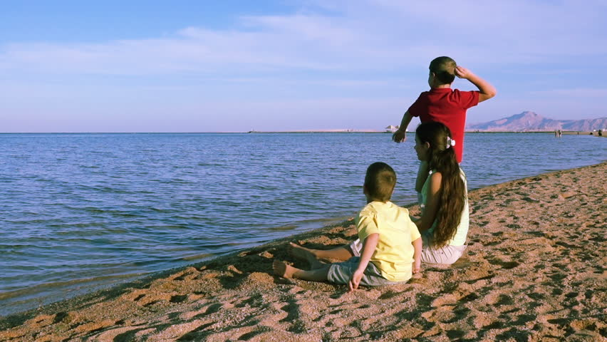 Three kids sitting at the coastline of Red sea in Egypt, Sharm El Sheikh