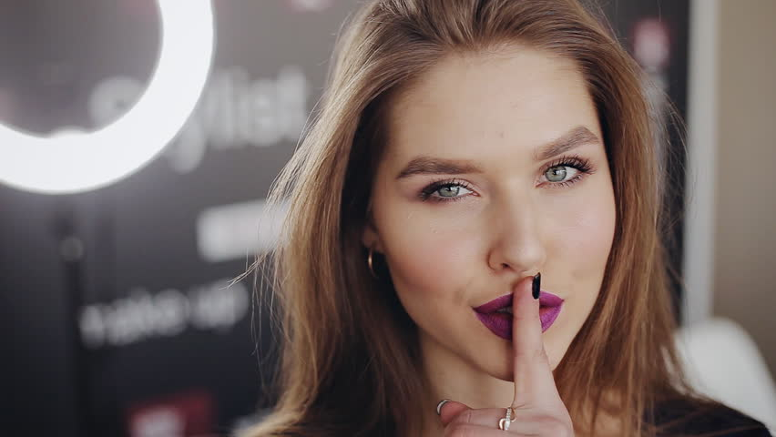 Beauty portrait of fashion young woman with finger on her lips showing gesture for silence