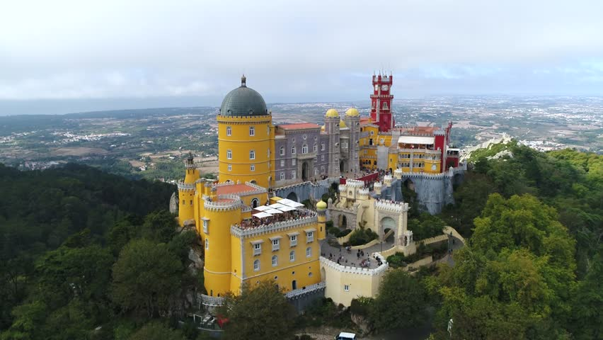 Aerial view of the iconic Pena National Palace moving towards building originally built on Monastery of Nossa Senhora da Pena and renovated extensively through initiative of Ferdinand II of Portugal