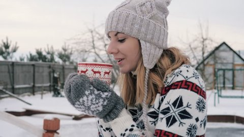 Caucasian woman in warm christmas clothes drinking hot tea or coffee from cup at cozy snowy house garden on winter morning. Enjoying winter outdoors with mug of warm drink. Slow motion, 4k, 3840x2160.