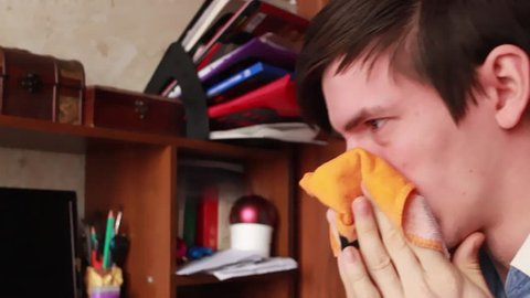 young guy has a runny nose, wipes his nose with a handkerchief, sneezes into his handkerchief